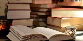 Åpen bok med bøker i bakgrunnen
